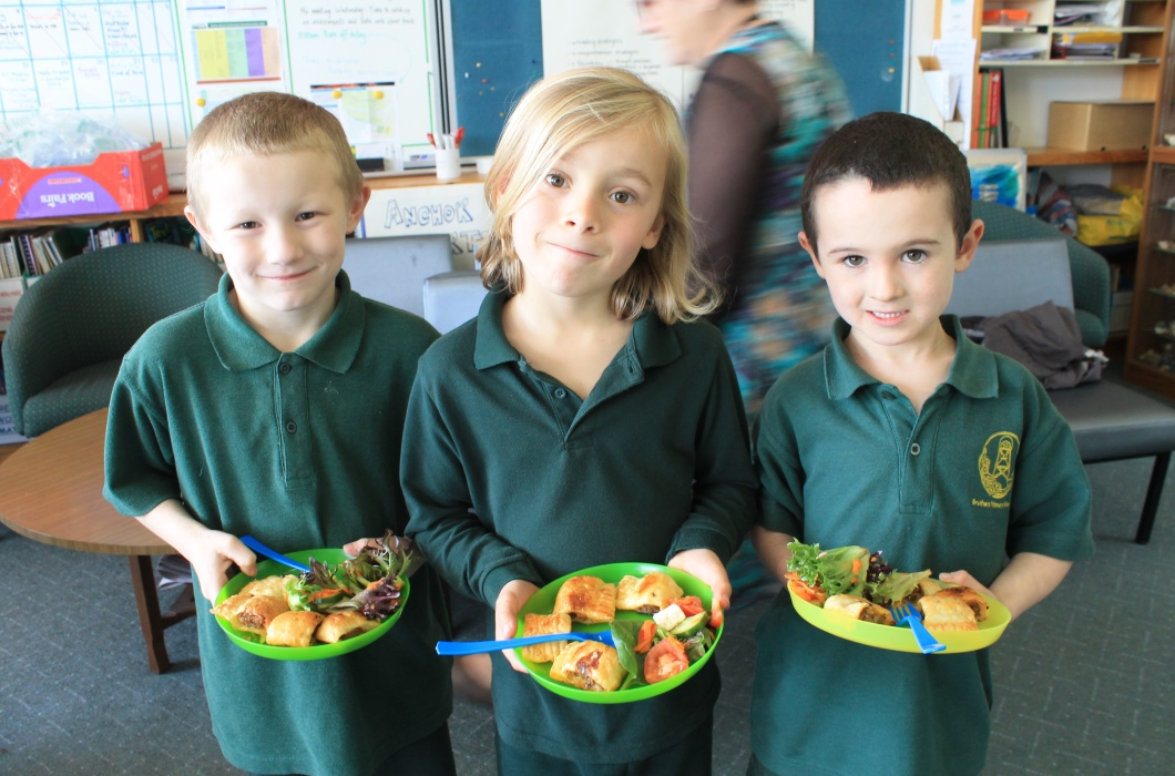 Three young primary school students, standing and holding plates of healthy food.